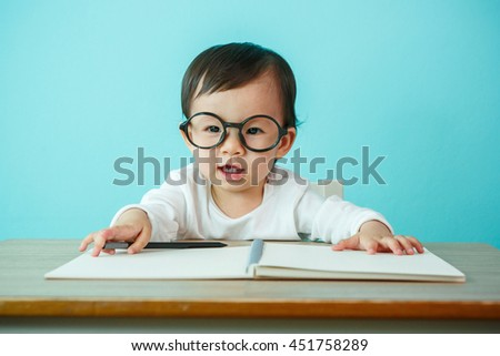 Portrait of an adorable baby girl wearing glasses on the table (soft focus on the eyes) - stock photo
