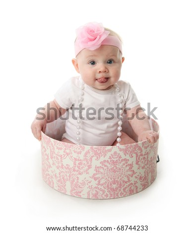 Portrait of an adorable baby girl with tongue sticking out sitting in a pink and white hatbox wearing a white shirt, pearl necklace, and pink headband with rose - stock photo