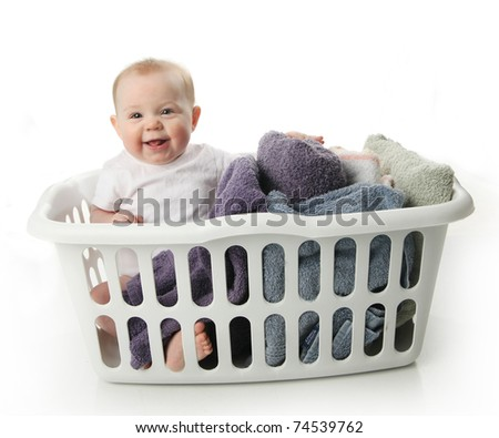 Portrait of an adorable baby sitting in a laundry basket with towels - stock photo
