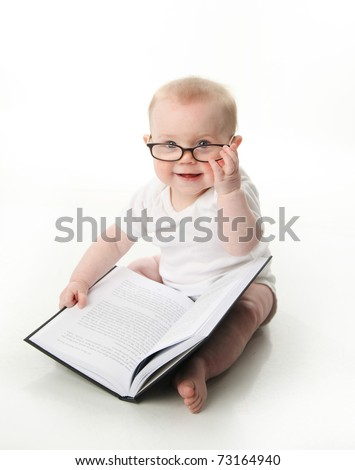 Portrait of an adorable baby sitting up wearing eyeglasses and looking at a book, isolated on white - stock photo