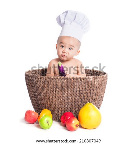 Portrait of an adorable baby wearing a chef hat with healthy fruit, isolated on white - stock photo