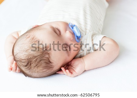 Portrait of an adorable baby with a pacifier sleeping in a bed at home - stock photo