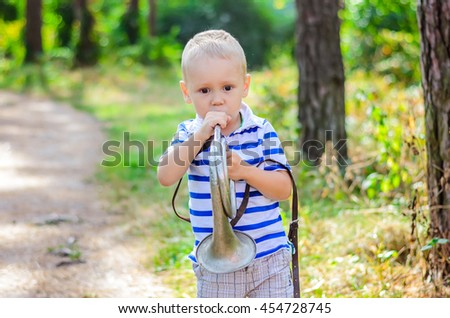 portrait of an adorable boy playing on a silver trumpet   - stock photo