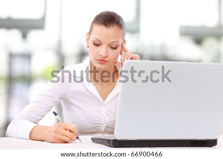 Portrait of an adorable business woman working at her desk - stock photo