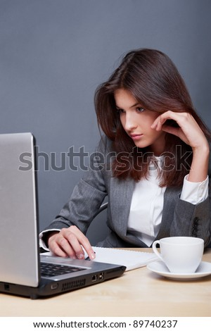 Portrait of an adorable business woman working at her desk with paperwork and laptop