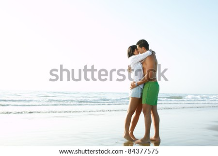 portrait of an adorable  couple in love kissing and embracing each other on the edge of the beach - stock photo