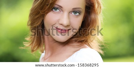 Portrait of an adorable girl with beautiful smile and eyes, who is hanging out in the park