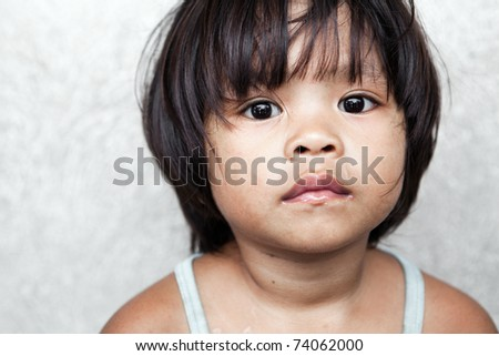 Portrait of an adorable, impoverished girl from the Philippines against wall. - stock photo