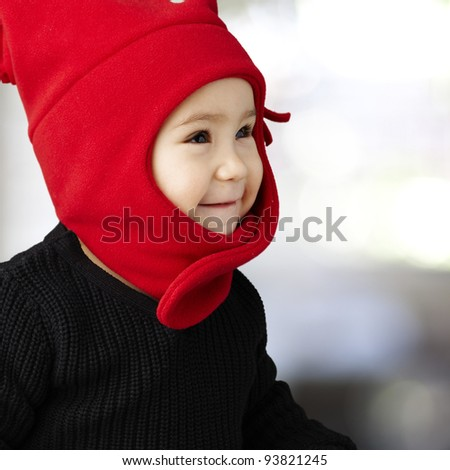 portrait of an adorable kid smiling and wearing winter clothes - stock photo
