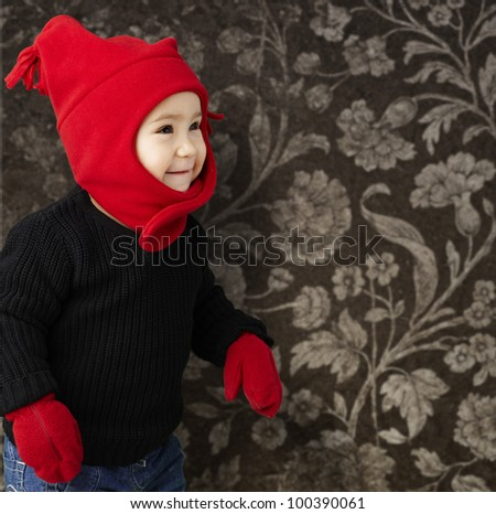 portrait of an adorable kid smiling wearing winter clothes against a vintage background - stock photo