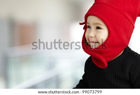 portrait of an adorable kid smiling wearing winter clothes indoor - stock photo