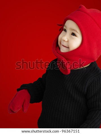 portrait of an adorable kid smiling wearing winter clothes over red - stock photo