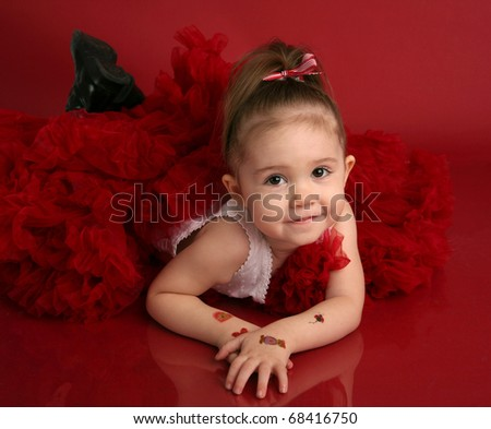 Portrait of an adorable little girl dressed in red on a red background for Valentines day or Christmas, with fake tattoos on her arms - stock photo