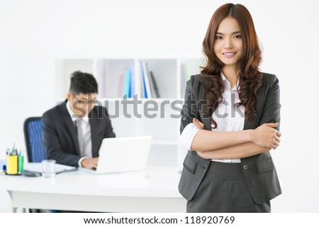 Portrait of an adorable office lady posing for the camera while her male associate working in the background - stock photo