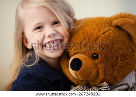 Portrait of an adorable preschool age girl playing with a teddy bear - stock photo