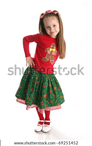 Portrait of an adorable preschool age girl wearing a Christmas holiday outfit with a gingerbread man and candy canes - stock photo