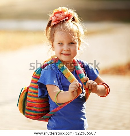 Portrait of an adorable preschool age girl with colorful knitted backpack. Preparation for school - stock photo
