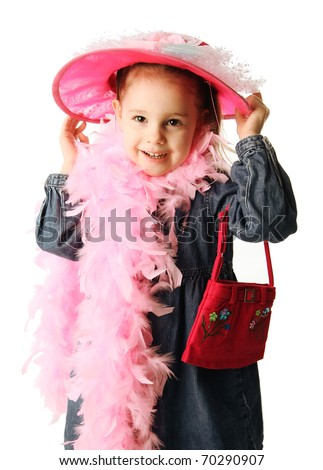 Portrait of an adorable preschool girl playing dress up with a fancy hat, purse, and pearl necklace isolated on white - stock photo