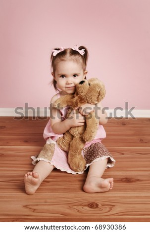 Portrait of an adorable toddler girl hugging a teddy bear on a vintage pink background