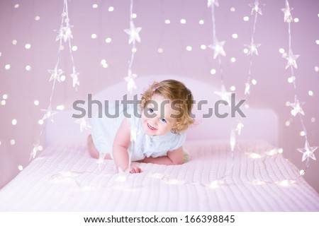 Portrait of an adorable toddler girl with beautiful curly hair playing on a white bed between beautiful Christmas lights in pink color
