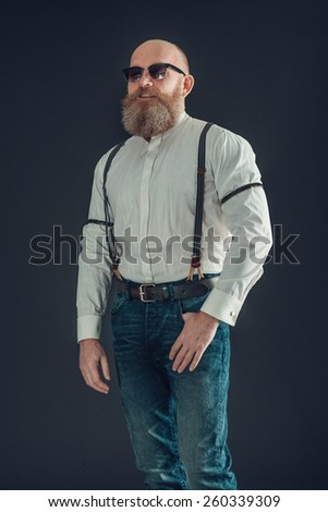 Portrait of an Adult Bald Goatee Man Wearing White Long Sleeves Shirt and Jeans with Suspenders on a Gray Background. - stock photo