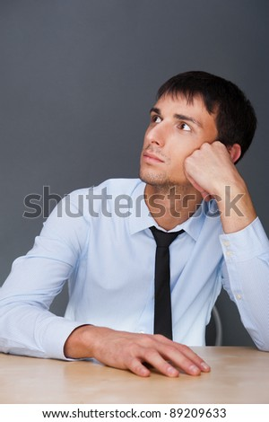 Portrait of an adult business man sitting in the office and daydreaming, planing