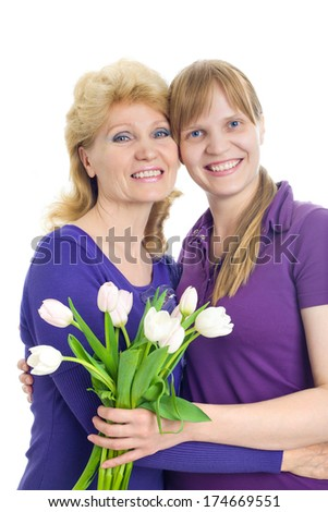 Portrait of an adult daughter and elderly mother with a bouquet of tulips - stock photo