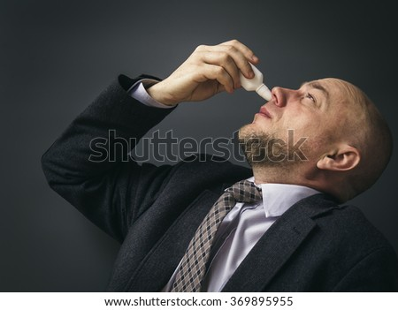Portrait of an adult man in a business suit on a black background. Businessman Suffering From Cold Spraying Nasal Spray In His Nose - stock photo