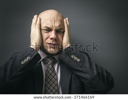 Portrait of an adult man in a business suit on a black background. Headache - stock photo