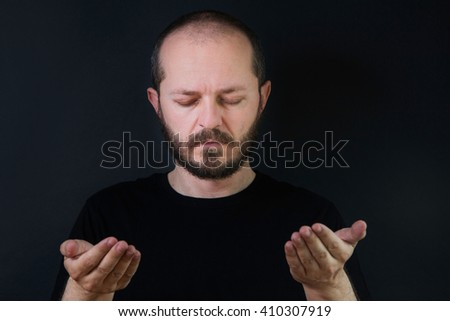 Portrait of an adult man with beard and mustaches on black background, eyes closed, praying and contemplating - stock photo