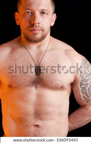 Portrait of an adult shirtless soldier with dog tags, black background
