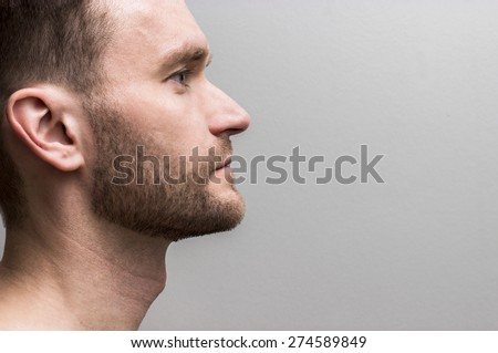 portrait of an adult white Caucasian man with a beard in profile, looking straight ahead, at the neutral grey background