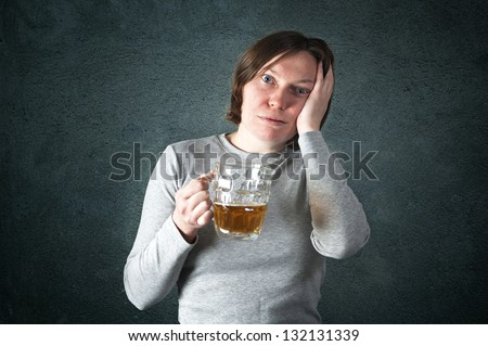 Portrait of an adult woman drinking beer, sad face - depression concept.