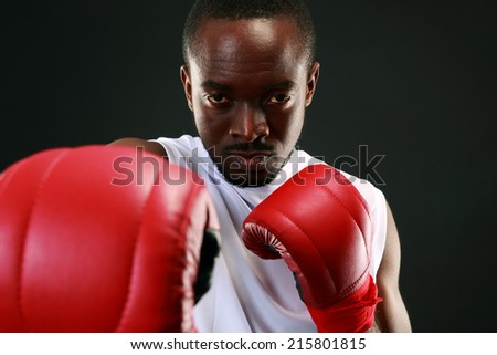Portrait of an African American boxer punching in camera - stock photo