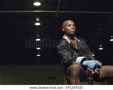 Portrait of an African American boxer sitting on chair - stock photo