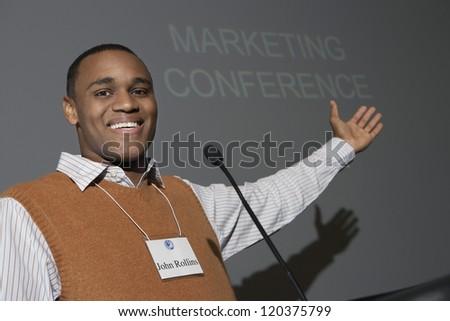 Portrait of an African American businessman gesturing towards blackboard during a speech - stock photo