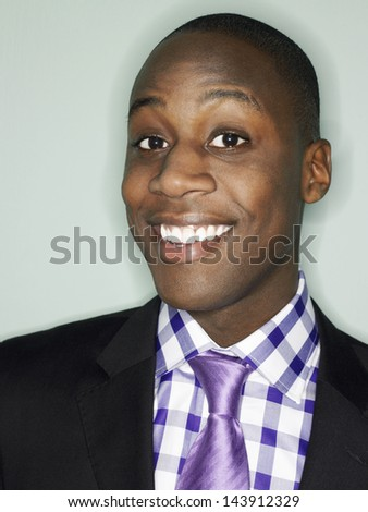 Portrait of an African American businessman smiling against light blue background - stock photo