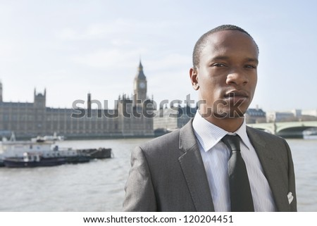 Portrait of an African American businessman standing in front of river - stock photo