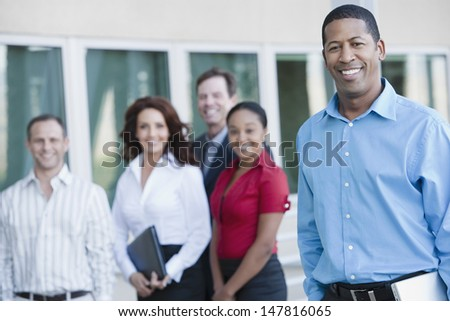 Portrait of an African American businessman with multiethnic executives in the background