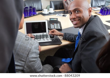 Portrait of an African American businessman working with colleague in office - stock photo