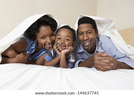Portrait of an African American couple with son lying underneath sheet