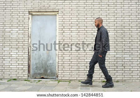 Portrait of an african american fashion model walking in urban environment - stock photo