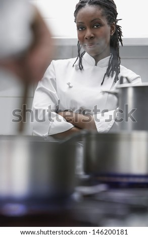 Portrait of an African American female chef in the kitchen - stock photo