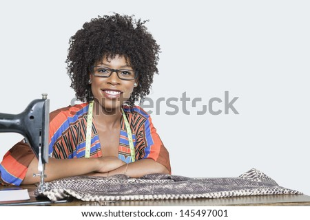 Portrait of an African American female fashion designer with sewing machine and cloth over gray background - stock photo