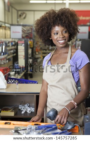 Portrait of an African American female store clerk standing at checkout counter scanning item - stock photo