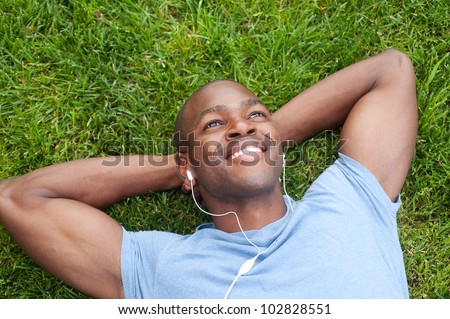 portrait of an African American man lying in grass listening to music - stock photo