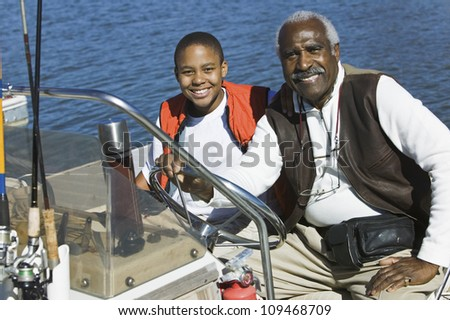 Portrait of an African American man sitting with grandson in a boat - stock photo