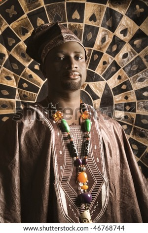 Portrait of an African American man wearing traditional African clothing, in front of a patterned wall and looking at the camera. Vertical format. - stock photo