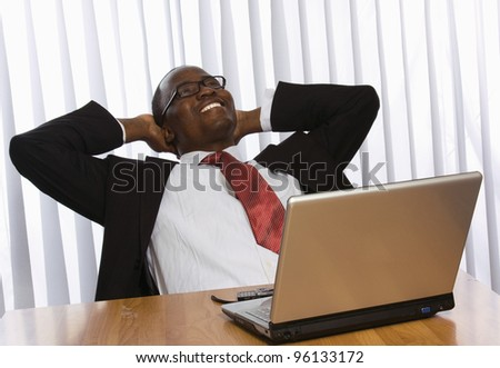 Portrait of an African American sitting on the desk with laptop - stock photo