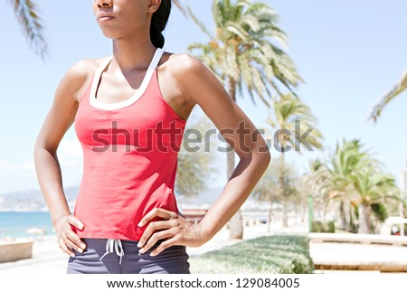 "Portrait of an ""african american"" sport woman after exercising in a coastal city by the beach,  proudly standing against a blue sky. - stock photo"